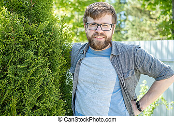 Satisfied male gardener hugs the thuja he raised and smiles sweetly in the garden on a summer day.