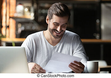 Satisfied millennial businessman reading paper letter with good news
