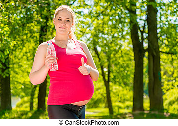 Satisfied pregnant woman posing with a bottle of water in the park