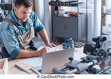 Satisfied self-employed engineer working at desk with...