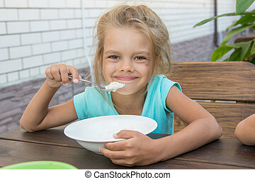Satisfied six year old girl at the table in the courtyard eating porridge