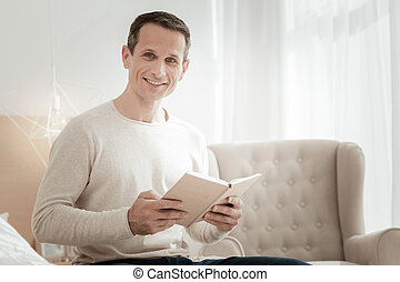Satisfied smart man holding a book and smiling.