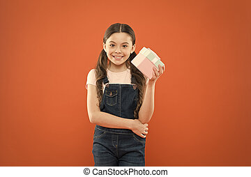 Satisfied with shopping. Small child holding gift box on orange background. Little girl after shopping for gift. Cute kid enjoying shopping. Shopping addict with present wrapped in box