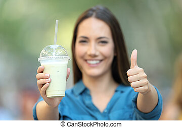 Satisfied woman holding a smoothie with thumbs up