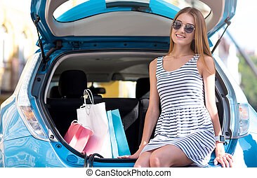 Satisfied woman sitting on trunk of car
