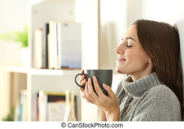 Satisfied woman smelling coffee in winter at home