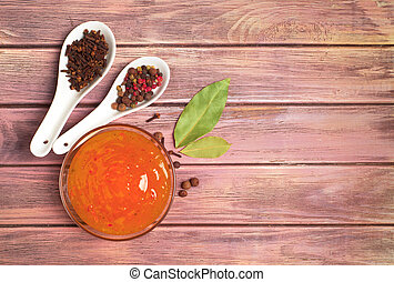 sauce and spices on a wooden background