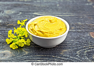 Sauce mustard in bowl with flower on dark board