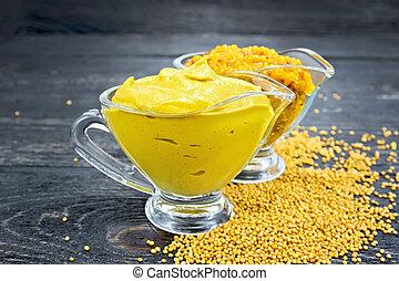 Sauce mustard in two sauceboats on dark board