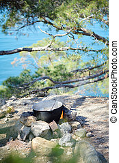 Saucepan hanging over the fire on rocks at seacoast tourist camp