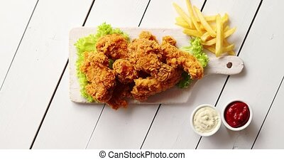 Sauces and French fries near lettuce and chicken wings -...