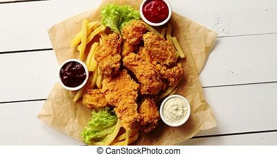 Sauces and lettuce near French fries and chicken wings -...