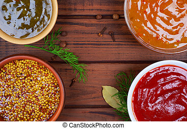 sauces in bowls on a wooden background