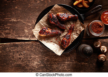 Saucy Barbecued Chicken Drumsticks on Iron Pan - High Angle...