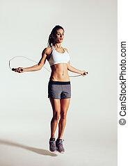 saudável, mulher jovem, corda saltando, em, estúdio