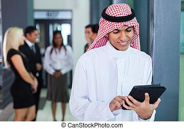 saudi arabian businessman using tablet computer in modern...