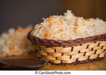Sauerkraut in bowl on wooden plate