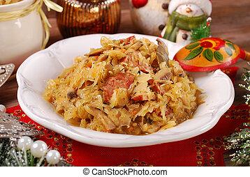 plate of traditional bigos (sauerkraut) with mushrooms and sausage for christmas