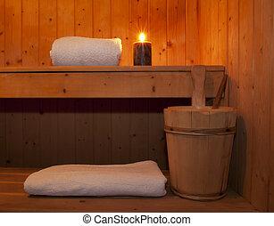 Sauna - Inside a wooden sauna, towel, candle and bucket