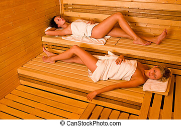 Sauna two women relaxing lying wrapped towel - Sauna two...
