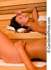 Sauna two women relaxing sweating naked bodies