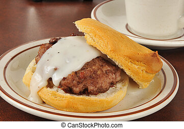 Sausage and biscuits with gravy - A sausage patty on a fresh...