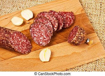 sausage and garlic on cutting board