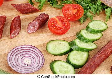 Sausage and vegetables on wooden platter.