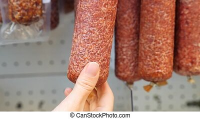 sausage on the counter in the store. The hand touches the sausage. 4k. Close-up. slow-motion