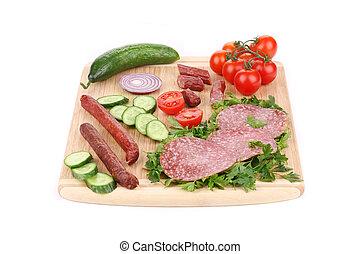 Sausage salami and vegetables on wooden platter.