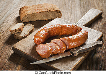 Sausage - the sliced tasty sausage with bread on the wooden...