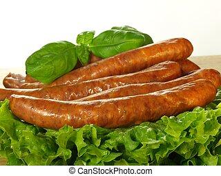 Sausage with lettuce, closeup - Sausage sticks with fresh...