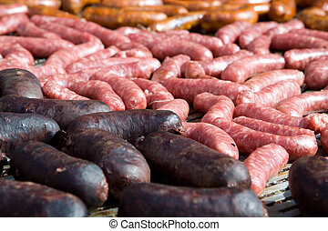 Sausages - A large group of sausages grilling