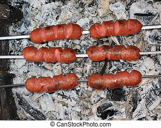 Sausages above hot embers