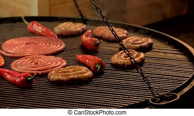 Sausages and chili peppers. Food being cooked on grill.