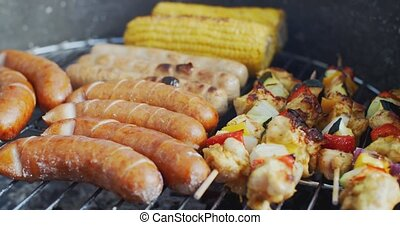 Sausages corn and veggie kebabs on a BBQ - Sausages corn and...