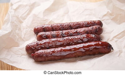 Sausages fried with sauce on parchment paper on table