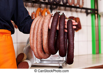 Sausages Hanging On Butcher's Hand - Closeup of sausages...