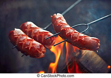 Sausages over the bondfire in nature - selective focus