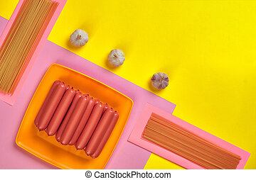 Sausages with spaghetti and garlic on a yellow and pink minimal background. Flat lay. Top view.