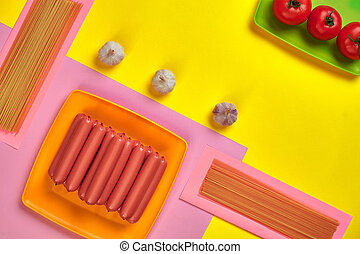 Sausages with tomatoes, spaghetti and garlic on a yellow and pink minimal background. Flat lay. Top view.
