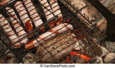 Sausages wrapped in bacon cooking on the grill.