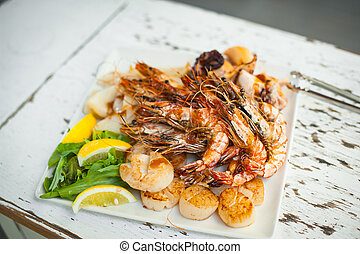 Saute shrimps, scallop, squid and lemon on white plate in the restaurant.