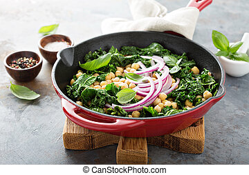 Sauteed kale with chickpeas and red onion - vegan dish in a...