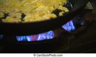 Sauteing onions in butter - A close up shot of onions being...