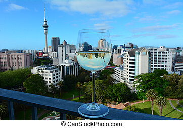 Sauvignon Blanc glass against Auckland skyline - Selective...