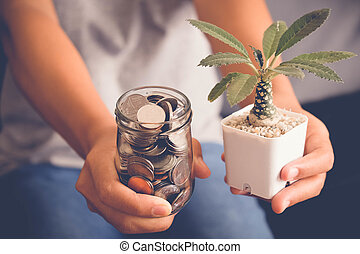 save money for investment concept Hand holding money in jar...