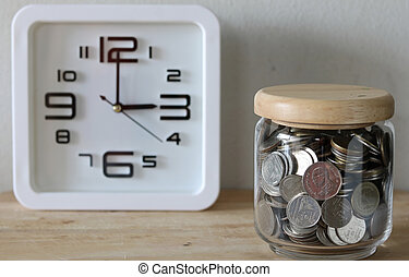 save money for investment concept money in the glass , a clock is behind the scenes