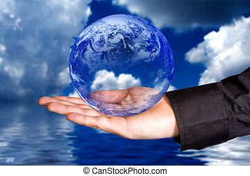 Protect the environment concept: human hand holding the Earth with clouds and water in background