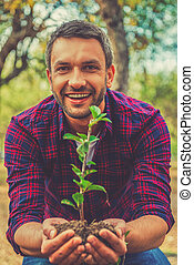 Save the environment! Happy young man stretching out plant in the ground and looking at camera while standing in the garden